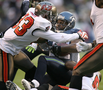 SEATTLE - DECEMBER 20:  Running back Julius Jones #22 of the Seattle Seahawks is tackled by Elbert Mack #33 of the Tampa Bay Buccaneers on December 20, 2009 at Qwest Field in Seattle, Washington. The Buccaneers defeated the Seahawks 24-7. (Photo by Otto G