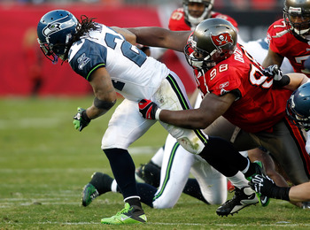 TAMPA, FL - DECEMBER 26: Defensive tackle Frank Okam #98 of the Tampa Bay Buccaneers tackles running back Marshawn Lynch #24 of the Seattle Seahawks during the game at Raymond James Stadium on December 26, 2010 in Tampa, Florida. (Photo by J. Meric/Getty