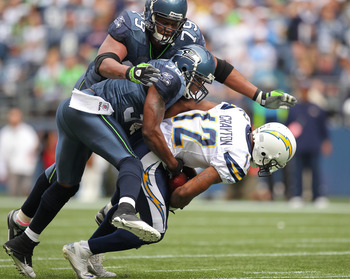 SEATTLE - SEPTEMBER 26:  Wide receiver Patrick Crayton #12 of the San Diego Chargers is tackled by Lawyer Milloy #36 and Red Bryant #79 of the Seattle Seahawks at Qwest Field on September 26, 2010 in Seattle, Washington. (Photo by Otto Greule Jr/Getty Ima