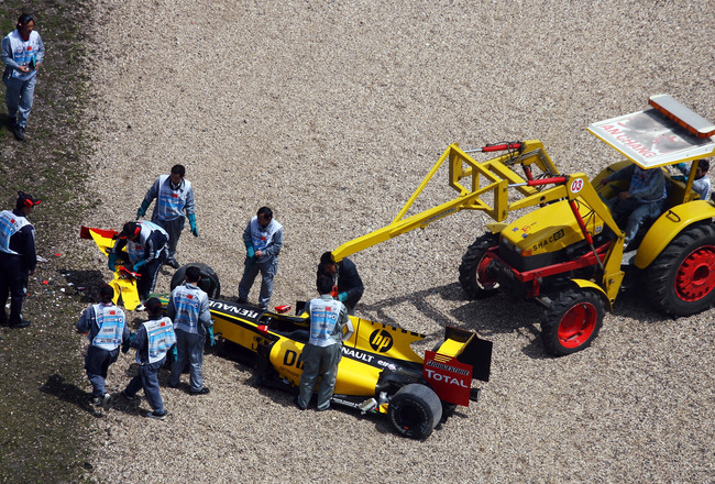 SHANGHAI, CHINA - APRIL 17:  The crash damaged car of Vitaly Petrov of Russia and Renault is attended to by race marshalls during the final practice session prior to qualifying for the Chinese Formula One Grand Prix at the Shanghai International Circuit o