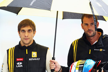 SUZUKA, JAPAN - OCTOBER 09:  Vitaly Petrov (L) of Russia and Renault walks to his team garage as torrential rain descends on the final practice session prior to qualifying for the Japanese Formula One Grand Prix at Suzuka Circuit on October 9, 2010 in Suz