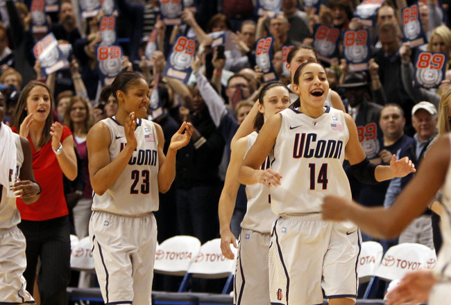 HARTFORD, CT - DECEMBER 21:  Samarie Walker #11, Maya Moore #23 and Bria Hartley #14 of the Connecticut celebrate a win over Florida State on December 21, 2010 in Hartford, Connecticut.  Connecticut set a record with 89 straight wins without a defeat. (Ph