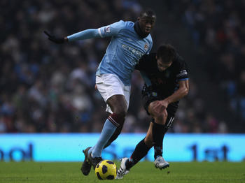 MANCHESTER, ENGLAND - DECEMBER 28:  Yaya Toure of Manchester City holds off a challenge from Stiliyan Petrov of Aston Villa during the Barclays Premier League match between Manchester City and Aston Villa at the City of Manchester Stadium on December 28,