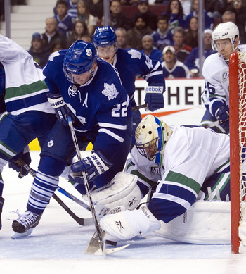 VANCOUVER, CANADA - DECEMBER 18: Goalie Roberto Luongo #1 of the Vancouver Canucks covers up the puck before Francois Beauchemin #22 of the Toronto Maple Leafs can get his stick on the loose puck during the third period in NHL action on December 18, 2010