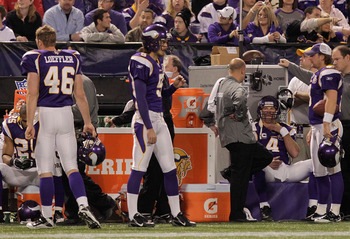 MINNEAPOLIS, MN - DECEMBER 05:  Brett Favre #4 (right) of the Minnesota Vikings sits on the sideline  against the Buffalo Bills defense at the Mall of America Field at the Hubert H. Humphrey Metrodome on December 5, 2010 in Minneapolis, Minnesota.  (Photo