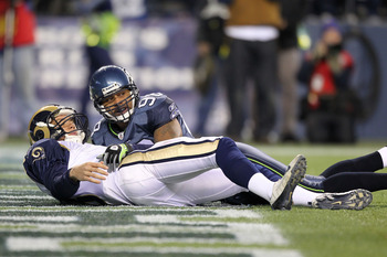 SEATTLE, WA - JANUARY 02:  Quarterback Sam Bradford #8 of the St. Louis Rams lays on the ground after being hit by defensive end Raheem Brock #98 of the Seattle Seahawks during their game at Qwest Field on January 2, 2011 in Seattle, Washington.  (Photo b