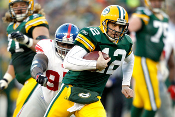 GREEN BAY, WI - DECEMBER 26:  Aaron Rodgers #12 of the Green Bay Packers is chased out of the pocket against the New York Giants at Lambeau Field on December 26, 2010 in Green Bay, Wisconsin.  (Photo by Matthew Stockman/Getty Images)