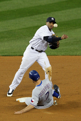 NEW YORK - OCTOBER 19:  Robinson Cano #24 of the New York Yankees turns a successful double play in the ninth inning over a sliding David Murphy #7 of the Texas Rangers in Game Four of the ALCS during the 2010 MLB Playoffs at Yankee Stadium on October 19,