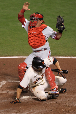 SAN FRANCISCO - OCTOBER 20:  Andres Torres #56 of the San Francisco Giants slides safely under the legs of Carlos Ruiz #51 of the Philadelphia Phillies to score a run in the in the fifth inning off a Aubrey Huff #17 RBI single in Game Four of the NLCS dur