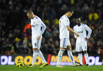 BARCELONA, SPAIN - NOVEMBER 29:  Karim Benzema and Cristiano Ronaldo of Real Madrid react after David Villa scored his second goal to make the score 4-0 in Barcelona's favour during the La Liga match between Barcelona and Real Madrid at the Camp Nou Stadi