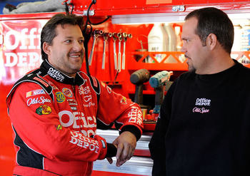 TALLADEGA, AL - OCTOBER 29:  Tony Stewart (L), driver of the #14 Old Spice/Office Depot Chevrolet, talks with crew chief Darian Grubb in the garage during practice for the NASCAR Sprint Cup Series AMP Energy Juice 500 at Talladega Superspeedway on October