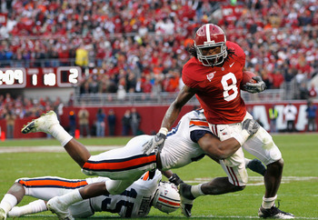 TUSCALOOSA, AL - NOVEMBER 26:  Julio Jones #8 of the Alabama Crimson Tide is tackled by Neiko Thorpe #15 and Eltoro Freeman #21 of the Auburn Tigers at Bryant-Denny Stadium on November 26, 2010 in Tuscaloosa, Alabama.  (Photo by Kevin C. Cox/Getty Images)