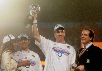 MIAMI GARDENS, FL - FEBRUARY 04:  Quarterback Peyton Manning #18 of the Indianapolis Colts celebrates with the Vince Lombardi Super Bowl trophy next to head coach Tony Dungy and is wife, Lauren, and CBS sports broadcaster Jim Nantz after winning the Super