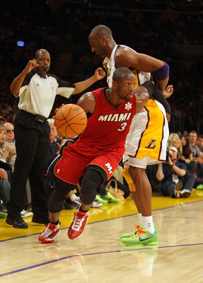 LOS ANGELES, CA - DECEMBER 25: Dwyane Wade #3 of the Miami Heat dribbles the ball to the basket as Kobe Bryant #24 of the Los Angeles Lakers gets called for a blocking foul during the NBA game at Staples Center on December 25, 2010 in Los Angeles, Califor