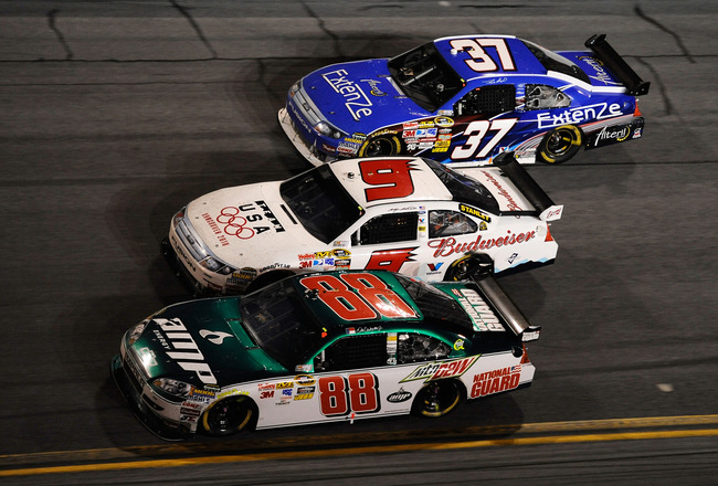 DAYTONA BEACH, FL - FEBRUARY 14:  Dale Earnhardt Jr., driver of the #88 AMP Energy/National Guard Chevrolet, races Kasey Kahne, driver of the #9 Budweiser Ford, and Travis Kvapil, driver of the #37 Extenze Ford, during the NASCAR Sprint Cup Series Daytona