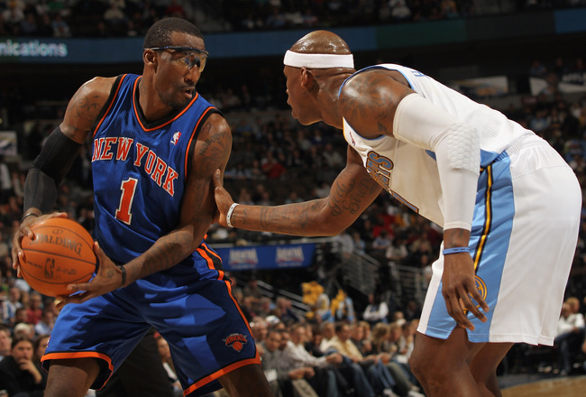 DENVER - NOVEMBER 16:  Amar'e Stoudemire #1 of the New York Knicks controls the ball as Al Harrington #7 of the Denver Nuggets defends at the Pepsi Center on November 16, 2010 in Denver, Colorado. NOTE TO USER: User expressly acknowledges and agrees that,