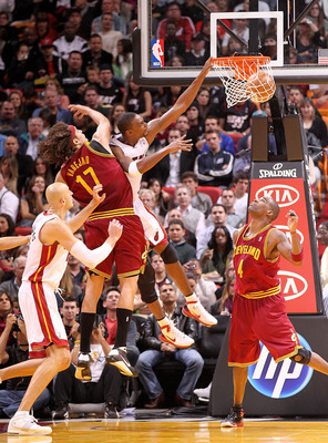 MIAMI, FL - DECEMBER 15:  Chris Bosh #1 of the Miami Heat dunks over Anderson Varejao #17 of the Cleveland Cavaliers during a game at American Airlines Arena on December 15, 2010 in Miami, Florida. NOTE TO USER: User expressly acknowledges and agrees that