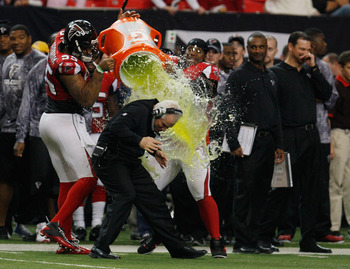 ATLANTA, GA - JANUARY 02:  Atlanta Falcons head coach Mike Smith is showered with Gatorade by players John Abraham #55 and Jonathan Babineaux #95 on the sideline during the game against the Carolina Panthers at the Georgia Dome on January 2, 2011 in Atlan