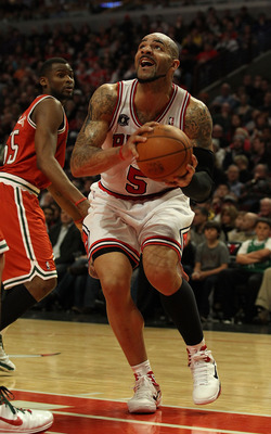 CHICAGO, IL - DECEMBER 28: Carlos Boozer #5 of the Chicago Bulls goes up for a shot past Keyon Dooling #55 of the Milwaukee Bucks at the United Center on December 28, 2010 in Chicago, Illinois. The Bulls defeated the Bucks 90-77. NOTE TO USER: User expres