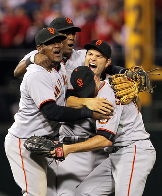 PHILADELPHIA - OCTOBER 23:  Freddy Sanchez #21, Juan Uribe #5, Edgar Renteria #16 and Nate Schierholtz #12 of the San Francisco Giants celebrate defeating the Philadelphia Phillies 3-2 and winning the pennant in Game Six of the NLCS during the 2010 MLB Pl