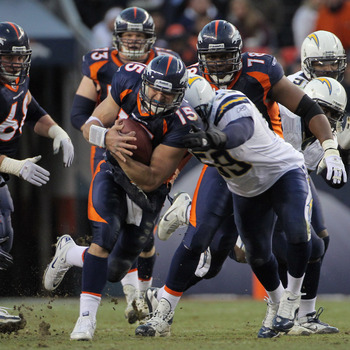 DENVER - JANUARY 02:  Quarterback Tim Tebow #15 of the Denver Broncos rushes with the ball as linebacker Brandon Siler #59 of the San Diego Chargers makes the tackle at INVESCO Field at Mile High on January 2, 2011 in Denver, Colorado. The Chargers defeat