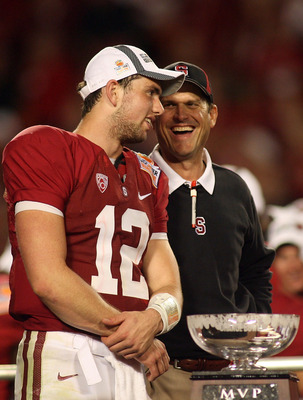 MIAMI, FL - JANUARY 03:  (L-R) Quarterback Andrew Luck and head coach Jim Harbaugh of the Stanford Cardinal celebrate with the trophy on stage after Stanford won 40-12 against the Virginai Tech Hokies during the 2011 Discover Orange Bowl at Sun Life Stadi