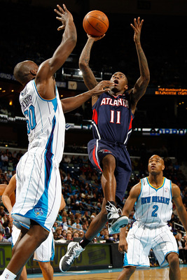 NEW ORLEANS, LA - DECEMBER 26:  Jamal Crawford #11 of the Atlanta Hawks shoots the ball over Emeka Okafor #50 of the New Orleans Hornets at the New Orleans Arena on December 26, 2010 in New Orleans, Louisiana.  The Hornets defeated the Hawks 93-86.  NOTE