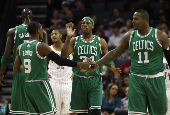 CHARLOTTE, NC - DECEMBER 11:  Teammates Paul Pierce #34 Rajon Rondo #9 and Glen Davis #11 of the Boston Celtics celebrate after a basket against the Charlotte Bobcats during their game at Time Warner Cable Arena on December 11, 2010 in Charlotte, North Ca
