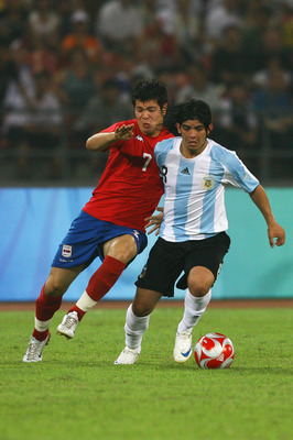BEIJING - AUGUST 13:  Ever Banega of Argentina is tackled by Milan Smiljanic #7 of Serbia during the Men's First Round Group A match between Argentina and Serbia at the Workers' Stadium on Day 5 of the Beijing 2008 Olympic Games on August 13, 2008 in Beij