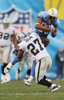 SAN DIEGO - DECEMBER 05:  Wide receiver Malcolm Floyd #80 of the San Diego Chargers is tackled by Stevie Brown #27 of the Oakland Raiders in the third quarter at Qualcomm Stadium on December 5, 2010 in San Diego, California. The Raiders defeated the Charg