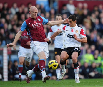 BIRMINGHAM, ENGLAND - NOVEMBER 13:  Javier Hernandez of Manchester United is challenged by James Collins of Aston Villa during the Barclays Premier League match between Aston Villa and Manchester United at Villa Park on November 13, 2010 in Birmingham, En