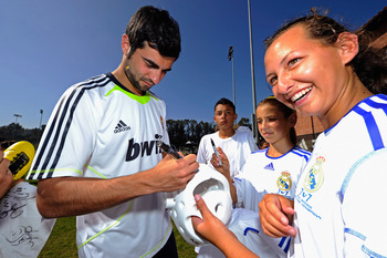 LOS ANGELES, CA - AUGUST 05:  Raul Albiol #18 of Real Madrid signs a soccer shirt for a local youth soccer player after participating in the Adidas training August 5, 2010 in Westwood section of Los Angeles, California. (Photo by Kevork Djansezian/Getty I