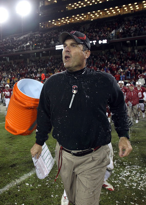 PALO ALTO, CA - NOVEMBER 27:  Head coach Jim Harbaugh of the Stanford Cardinal is covered with water from a Gatorade cooler by Andrew Luck #12 and Chike Amajoyi #43 after the Cardinal beat the Oregon State Beavers at Stanford Stadium on November 27, 2010