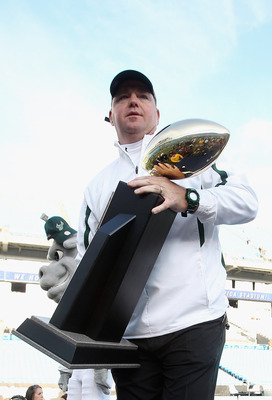 CHARLOTTE, NC - DECEMBER 31:  Head coach Skip Holtz of the USF Bulls stands with the trophy after a 31-26 victory over the Clemson Tigers at Bank of America Stadium on December 31, 2010 in Charlotte, North Carolina.  (Photo by Streeter Lecka/Getty Images)
