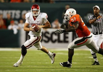 MIAMI GARDENS, FL - OCTOBER 03:  Quarterback Landry Jones #12 of the Oklahoma Sooners scrambles away from linebacker Allen Bailey #57 of the Miami Hurricanes at Land Shark Stadium on October 3, 2009 in Miami Gardens, Florida. Miami defeated Oklahoma 21-20