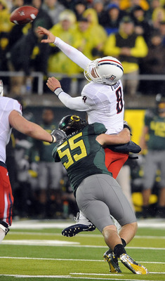 EUGENE, OR - NOVEMBER 26: Quarterback Nick Foles #8 of the Arizona Wildcats is hit by linebacker Casey Matthews #55 of the Oregon Ducks in the third quarter of the game at Autzen Stadium on November 26, 2010 in Eugene, Oregon. The Ducks won the game 48-29