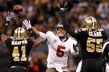 NEW ORLEANS, LA - JANUARY 02:  Quarterback Josh Freeman #5 of the Tampa Bay Buccaneers throws a pass over Roman Harper #41 and Danny Clark #55  of the New Orleans Saints at the Louisiana Superdome on January 2, 2011 in New Orleans, Louisiana.   The Buccan