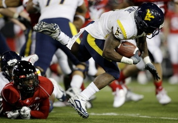 CINCINNATI - NOVEMBER 13:  Runningback Noel Devine #7 of the West Virginia Mountaineers is taken down in the third quarter of the game against the Cincinnati Bearcats in at Nippert Stadium on November 13, 2009 in Cincinnati, Ohio.  (Photo by Andy Lyons/Ge