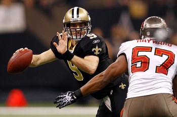 NEW ORLEANS, LA - JANUARY 02:  Quarterback Drew Brees #9 of the New Orleans Saints avoids a tackle by Adam Hayward #57 of the Tampa Bay Buccaneers at the Louisiana Superdome on January 2, 2011 in New Orleans, Louisiana.  (Photo by Chris Graythen/Getty Ima