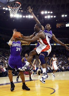 OAKLAND, CA - NOVEMBER 16:  Baron Davis #5 of the Golden State Warriors passes over Ron Artest #93 of the Sacramento Kings on November 16, 2006 at Oracle Arena in Oakland, California. NOTE TO USER: User expressly acknowledges and agrees that, by downloadi