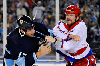 PITTSBURGH, PA - JANUARY 01:  John Erskine #4 of the Washington Capitals and Michael Rupp #17 of the Pittsburgh Penguins fight during the 2011 NHL Bridgestone Winter Classic at Heinz Field on January 1, 2011 in Pittsburgh, Pennsylvania.  (Photo by Jamie S