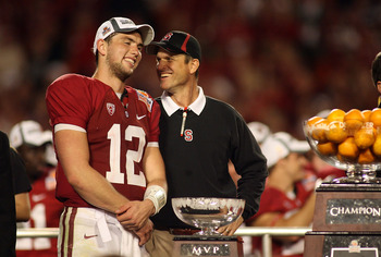 MIAMI, FL - JANUARY 03: (L-R) Quarterback Andrew Luck #12 and head coach Jim Harbaugh of the Stanford Cardinal celebrate with the trophy on stage after Stanford won 40-12 against the Virginia Tech Hokies during the 2011 Discover Orange Bowl at Sun Life St