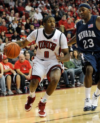 LAS VEGAS - NOVEMBER 18:  Oscar Bellfield #0 of the UNLV Rebels drives around Armon Johnson #23 of the Nevada Wolf Pack during their game at the Thomas & Mack Center on November 18, 2009 in Las Vegas, Nevada. UNLV won 88-75.  (Photo by Ethan Miller/Getty