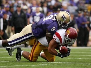 SEATTLE - SEPTEMBER 19:  Running back Stanley Havili #31 of the USC Trojans fumbles against Donald Butler #9 of the Washington Huskies in the third quarter on September 19, 2009 at Husky Stadium in Seattle, Washington. The Huskies defeated the Trojans 16-