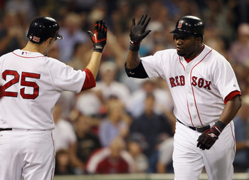 BOSTON - SEPTEMBER 22:  David Ortiz #34 of the Boston Red Sox is congratulated by teammate Miike Lowell #25 after Ortiz hit a three run homer in the fourth inning against the Baltimore Orioles on September 22, 2010 at Fenway Park in Boston, Massachusetts.