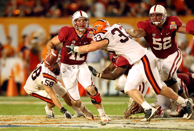 MIAMI, FL - JANUARY 03: Andrew Luck #12 of the Stanford Cardinal ellude Chris Drager #33 of the Virginia Tech Hokies during the 2011 Discover Orange Bowl at Sun Life Stadium on January 3, 2011 in Miami, Florida. STanford won 40-12. (Photo by Mike Ehrmann/