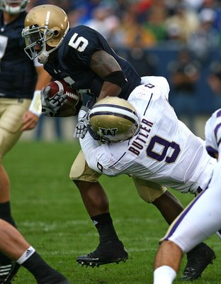 SOUTH BEND, IN - OCTOBER 03: Armando Allen #5 of the Notre Dame Fighting Irish is tackled by Donald Butler #9 of the Washington Huskies on October 3, 2009 at Notre Dame Stadium in South Bend, Indiana. Notre Dame defeated Washington 37-30 in overtime.  (Ph