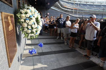 NEW YORK - JULY 16:  Fans of the New York Yankees line up to view the plaque of long time Yankee Stadium public address announcer Bob Sheppard in Monument Park prior to the game against the Tampa Bay Rays on July 16, 2010 in the Bronx borough of New York