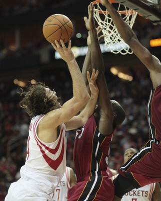 HOUSTON - DECEMBER 29: Luis Scola #4 of the Houston Rockets is foulded by Joel Anthony #50 of the Miami Heat as he drives to the basket in the second half at Toyota Center on December 29, 2010 in Houston, Texas. NOTE TO USER: User expressly acknowledges a