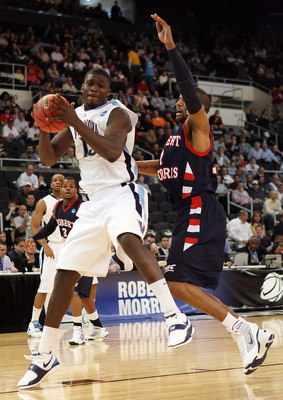 PROVIDENCE, RI - MARCH 18:  Mouphtaou Yarou #13  of the Villanova Wildcats heads for the basket as Rob Robinson #1 of the Robert Morris Colonials defends during the first round of the 2010 NCAA men's basketball tournament on March 18, 2010 at the Dunkin D